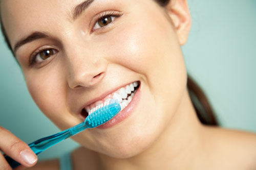 A close up of a woman brushing her teeth.