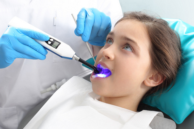 A young girl receiving a dental sealant.